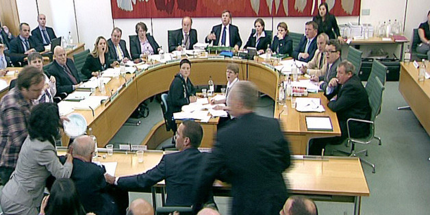 """Box office: Comedian """"Jonnie Marbles"""" confronts Rupert Murdoch with a paper plate covered in shaving foam as he gave evidence to the Culture, Media and Sport Select Committee on the News of the World phone-hacking scandal. Committees are not always this dramatic."""