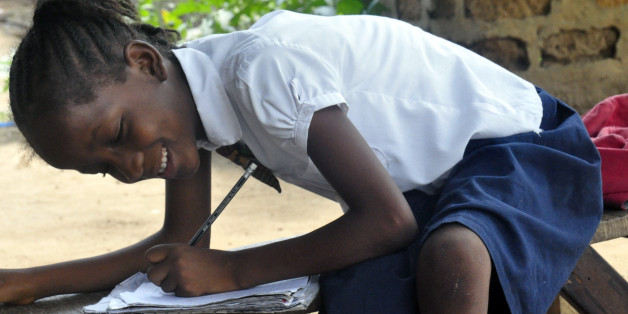 In this photo taken on Friday, May 8, 2015, Mercy Kennedy smiles as she does her home work after school at her home in Monrovia, Liberia. On the day Mercy Kennedy lost her mother to Ebola, it was hard to imagine a time Liberia would be free of one of the world's deadliest viruses. It had swept through the 9-year-old's neighborhood, killing people house by house. Now seven months later, Liberia on Saturday officially marked the end of the epidemic that claimed more than 4,700 lives here