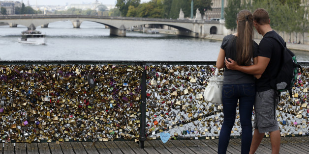 TO GO WITH AFP STORY BY BONIFACE MURUTAMPUNZI A couple looks at the Pont des Arts where padlocks are attached to the railing, on August 30, 2013 in Paris. Due to security reason authorities consider removing the 'Love locks' that have been attached to the Pont des Arts bridge since 2008 by thousand of lovers.AFP PHOTO / PATRICK KOVARIK        (Photo credit should read PATRICK KOVARIK/AFP/Getty Images)