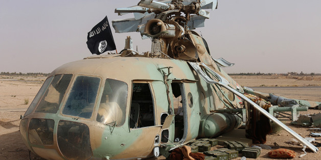 This photo released on Saturday, May 31, 2015 by a militant website, which has been verified and is consistent with other AP reporting, shows a flag of the Islamic State group placed on a damaged helicopter at Tadmur military airbase, which was captured by the Islamic State group in Palmyra in Homs province, Syria. The Syrian military has suffered a series of setbacks in northern Syria recently as insurgents captured the city of Idlib and almost all of Idlib province. The IS group has also seize