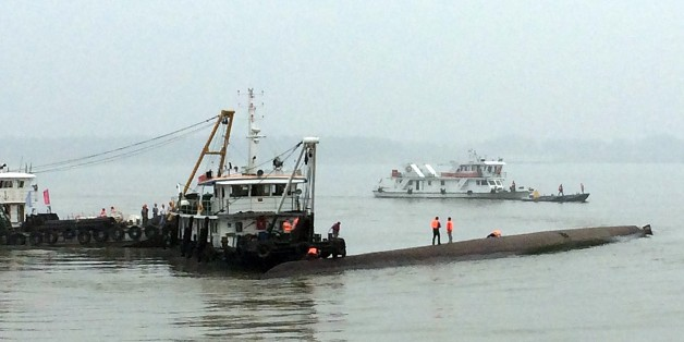 Chinese rescue boats are seen alongside a capsized passenger ship carrying more than 450 people which sunk in the Yangtze river, triggering a rescue effort hampered by strong winds and heavy rain off Jianli in China's Hubei province on June 2, 2015.  The ship named Dongfangzhixing, or 'Eastern Star', was headed from the eastern city of Nanjing to the southwestern city of Chongqing when it sank in the Jianli section of the river.           CHINA OUT      AFP PHOTO        (Photo credit should read