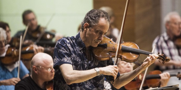 In this photo taken Wednesday, May 27, 2015, Grammy Award-winning American violinist Eugene Drucker, plays his violin during a rehearsal concert at the Music Hall in Raanana, central Israel. In 1933, the violinist Ernest Drucker left the stage midway through a Brahms concerto in Cologne at the behest of Nazi officials, in one of the first anti-Semitic acts of the new regime. Now, more than 80 years later, his son, Eugene, has completed his father's interrupted work. With tears in his eyes,