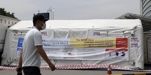 A man wearing mask walks near a precaution against the MERS, Middle East Respiratory Syndrome, virus at a quarantine tent for people who could be infected with the MERS virus at Seoul National University Hospital in Seoul, South Korea, Tuesday, June 2, 2015. South Korea on Tuesday confirmed the country's first two deaths from MERS as it fights to contain the spread of the virus that has killed hundreds of people in the Middle East. (AP Photo/Lee Jin-man)