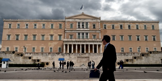 A woman walks in front of the Greek Parliament in Athens on April 7, 2015. Greek lawmakers voted on April 7 to set up a committee to examine the circumstances under which Greece agreed to bailouts totaling 240 billion euros (USD 260 billion) with the European Union and International Monetary Fund. AFP PHOTO / ARIS MESSINIS        (Photo credit should read ARIS MESSINIS/AFP/Getty Images)
