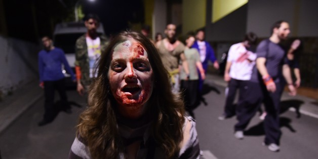 A woman wearing cinema style make-up to resemble the living dead walks along a street followed by a group during the role game 'Survival Zombie' in Olias del Rey on May 30, 2015.  Hundred of people gather in Olias del Rey to play in this edition of 'Survival Zombie' that runs from 11pm to 7am and is organised by Spanish company World Real Games.  AFP PHOTO / PIERRE-PHILIPPE MARCOU        (Photo credit should read PIERRE-PHILIPPE MARCOU/AFP/Getty Images)