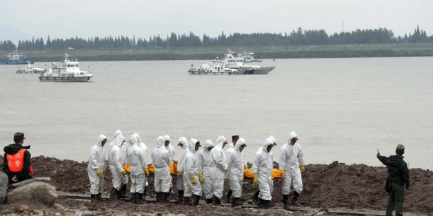 This picture taken on June 3, 2015 shows Chinese rescue workers removing the bodies of victims from the Chinese cruise ship which capsized three days ago in the Yangtze river in Jianli, in central China's Hubei province. Hundreds of relatives of passengers missing after their cruise ship capsized in central China gathered at the disaster site on June 4, as rescuers breached the hull in a last-ditch search for more than 400 people believed trapped inside.   CHINA OUT --  AFP PHOTO        (Photo c