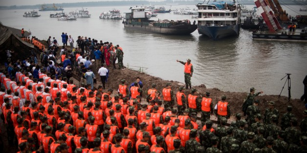 Chinese soldiers and rescue workers pay there respect to the victims during a memorial service in front of the raised Chinese cruise ship, in Jianli on June 7, 2015. Rescuers extended their search for victims of a Chinese cruise ship sinking to include a vast stretch of the Yangtze river Saturday, as the confirmed death toll rose to 396, marking the country's worst shipping disaster in nearly 70 years. AFP PHOTO / JOHANNES EISELE        (Photo credit should read JOHANNES EISELE/AFP/Getty Images)