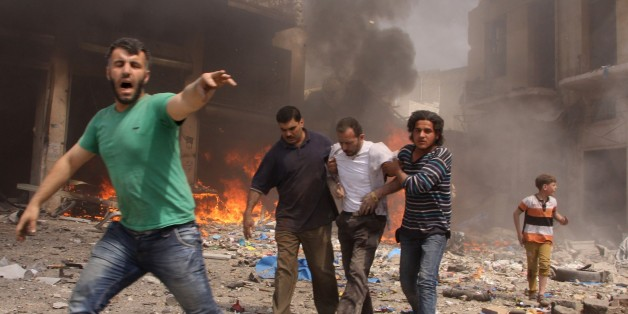 Syrian men react and help the inured following a reported barrel bomb attack by Syrian government forces that hit an open market in the northern city of Aleppo, on June 3, 2015, killing and injuring people. Regime barrel bombs -- crude weapons made of containers packed with explosives --  have often struck schools, hospitals, and markets in Syria. AFP PHOTO / KARAM AL-MASRI        (Photo credit should read KARAM AL-MASRI/AFP/Getty Images)