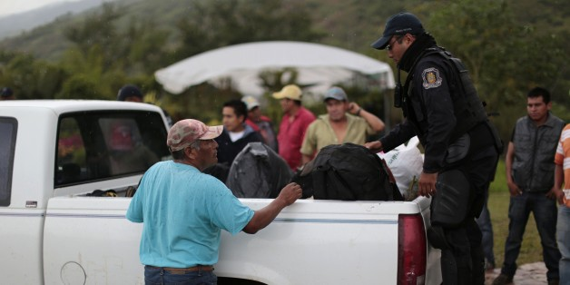 A member of the Guerrero state police (R) inspects the back of a truck at a checkpoint entering the city of Chilapa, in the Mexican state of Guerrero, on the eve of midterm elections, on June 6, 2015. Meanwhile, a self-defense militia was attacked by a rival faction in southern Mexico on June 6 leaving at least 10 people dead, witnesses said, amid tensions in the region on the eve of elections.  While the bloodshed in the village of Xolapa did not appear linked to the June 7 congressional, gubernatorial and municipal elections, it occurred in a state plagued by violence and protests ahead of the vote.      AFP PHOTO / PEDRO PARDO        (Photo credit should read Pedro PARDO/AFP/Getty Images)