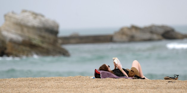 A woman reads a book on the beach in Biarritz on April 15, 2015. AFP PHOTO / GAIZKA IROZ        (Photo credit should read IROZ GAIZKA/AFP/Getty Images)