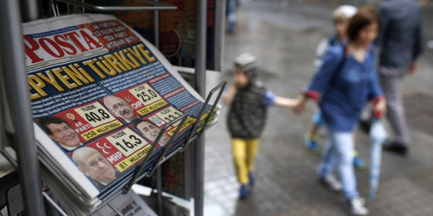 People walk past a kiosk with newspapers featuring front-page coverage of Sunday's elections, in Istanbul, Turkey, Monday, June 8, 2015. Turkey's long-ruling party has suffered surprisingly strong losses in parliament that will force it to seek a coalition partner for the next government, but other parties vowed to resist any pact as election results flowed in Monday. President Recep Tayyip Erdogan's Justice and Development Party, known as the AKP, won less than 41 percent of votes in Sunday's election for Turkey's 550-seat parliament. It was projected to take 258 seats, still top of the political heap but 18 below the minimum required to rule alone. (AP Photo/Emrah Gurel)