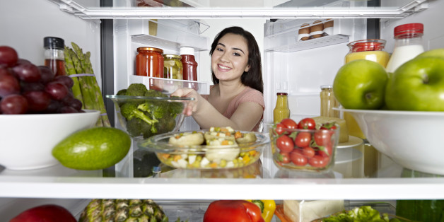 Woman looking at camera out of the fridge.