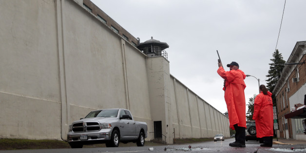 A state corrections officer monitors traffic passing Clinton Correctional Facility on Monday, June 8, 2015, in Dannemora, N.Y. Two murderers who escaped from the prison by cutting through steel walls and pipes remain on the loose Monday as authorities investigate how the inmates obtained the power tools used in the breakout.  (AP Photo/Mike Groll)