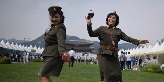 North Korean defectors wearing North Korean military uniforms dance in Gwanghwamun square during a 'unification expo' in central Seoul on May 29, 2015. The expo aims to raise awareness about inter-Korean unification. AFP PHOTO / Ed Jones        (Photo credit should read ED JONES/AFP/Getty Images)