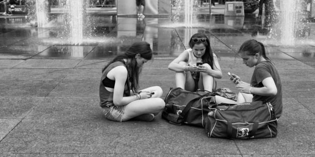 A few young women sit on the ground in Dundas Square using their cell phones. Yonge and Dundas Square