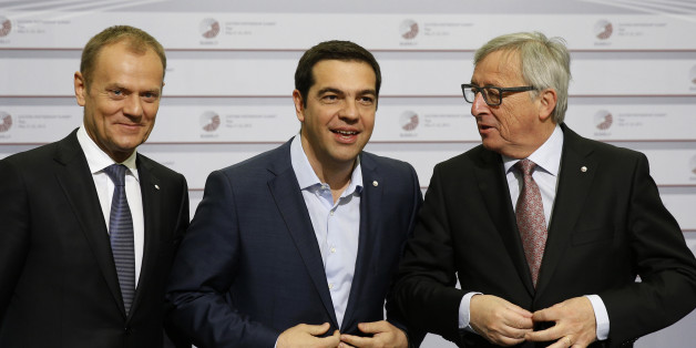European Commission President Jean-Claude Juncker, right, and Greek Prime Minister Alexis Tsipras, center, button their jackets as the stand with European Council President Donald Tusk during arrivals at the Eastern Partnership summit in Riga, on Friday, May 22, 2015. EU leaders gather for a second day of meetings with six post-communist nations to discuss various issues, including enlargement, the economy and Ukraine. (AP Photo/Mindaugas Kulbis)