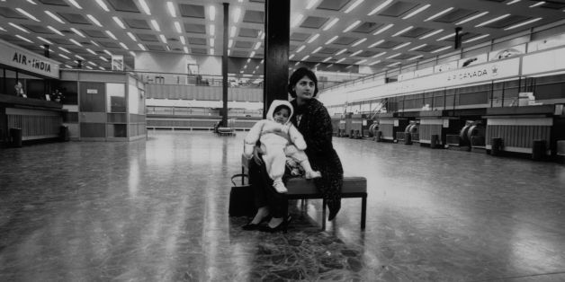 February 1968:  An Asian woman and her young baby, immigrants to Britain, sit in a deserted London airport.  (Photo by Roy Jones/Evening Standard/Getty Images)