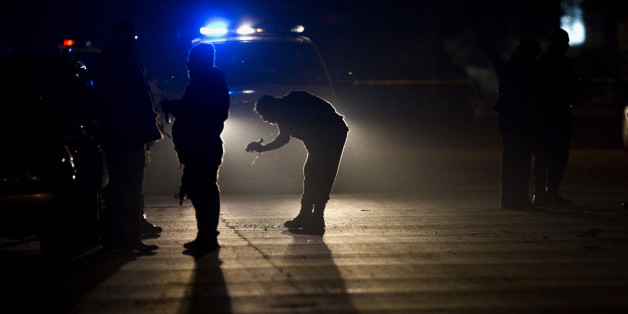 Investigators work at the scene where two men were murder in Tijuana, Mexico, late Friday, March 4, 2011. According to police, two men died and other was injured after being shot by unknown gunmen. (AP Photo/Guillermo Arias)
