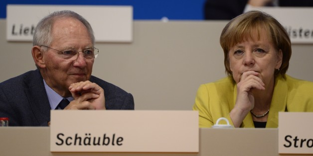 German Chancellor Angela Merkel (R) and German Finance Minister Wolfgang Schaeuble take part in the Christian Democratic Union (CDU) congress in Cologne, western Germany, on December 10, 2014. German Chancellor Angela Merkel was re-elected unopposed on December 9, 2014 as chief of her conservative party at a triumphant congress that celebrated her role as Europe's most powerful leader.     AFP PHOTO / JOHN MACDOUGALL        (Photo credit should read JOHN MACDOUGALL/AFP/Getty Images)
