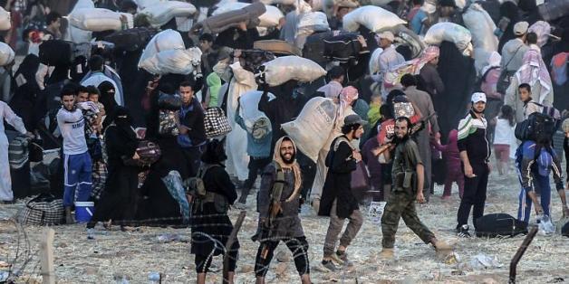 Des membres du groupe EI demandent aux habitants de retourner dans leur ville en Syrie, à la frontière avec la Turquie, le 13 juin 2015