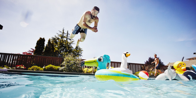 Man diving from pool deck towards inflatable pool toy in outdoor pool with friend watching in background