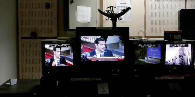 Greek Prime Minister Alexis Tsipras is seen on a TV monitor (C) at the control room during the news broadcast of state television ERT in Athens on June 11, 2015. Greece's public broadcaster ERT came back on the air on Thursday, exactly two years after it was shut down by the previous government, which accused it of being wasteful and mismanaged. AFP PHOTO / ANGELOS TZORTZINIS        (Photo credit should read ANGELOS TZORTZINIS/AFP/Getty Images)