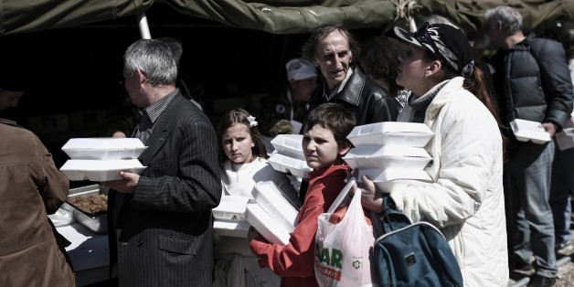 People line up to take free food which is distributed at a military camp near Athens on April 12, 2015. Greece's Defense ministry organized a free meal for the poor on Orthodox Easter. AFP PHOTO / ANGELOS TZORTZINIS        (Photo credit should read ANGELOS TZORTZINIS/AFP/Getty Images)