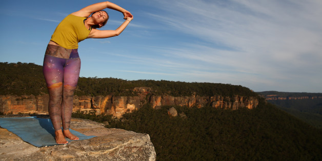 MT VICTORIA, AUSTRALIA - MARCH 07:  Thea Bainbridge of England practices yoga on the cliffs at Corroboree Walls in Mount Victoria on March 7, 2015 in the Blue Mountains, Australia. On March 6th  8th the highlining community from around the world ascended on Mount Victoria in the Blue Mountains two hours west of Sydney for a weekend of challenging lines and routes established between various cliffs in the mountains. Seven highlines of different spans and tension were rigged and participants of various skill levels and experience challenged themselves. The crowd that gathered shared a similar passion for adventure, the outdoors and relaxing together sharing stories and encouraging each other as they push their limits in the stunning Blue Mountains National Park. Growing in popularity the relatively new sport seems dangerous and extreme, however safety is paramount with numerous safety harnesses and procedures are implemented to maintain a well measured and safe environment. Slacklining is a balance sport in which participants walk on a flat nylon webbing anchored between two points with the tension adjusted to allow for slack, providing an experience similar to that of walking on a trampoline. Highlining is a style of slacklining where the two anchor points are set up with significant elevation from the ground or water below known as exposure. Unlike extreme sports such as skydiving or bungee jumping, the participant has to make constant decisions and mentally overcome their fear and harness their adrenalin compared to making that one initial choice to jump in the case of the other sports. Numerous highliners are confident walking a slackline of the same distance in a park low to the ground, however the mental challenge at heights with the view below and environmental elements to contend with proves a much tougher challenge.  (Photo by Cameron Spencer/Getty Images)
