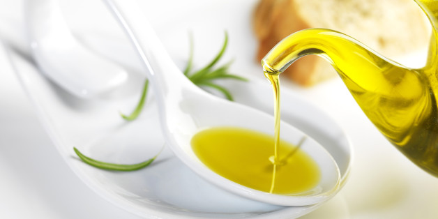 bottle pouring virgin olive oil in a porcelain spoon