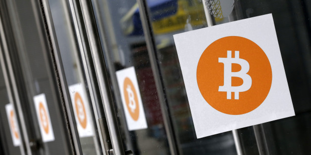 Bitcoin logos are displayed at the Inside Bitcoins conference and trade show, Monday, April 7, 2014 in New York. Bitcoin users exchange cash for digital money using online exchanges, then store it in a computer program that serves as a wallet. The program can transfer payments directly to merchants or individuals around the world, eliminating transaction fees and the need for bank or credit card information. (AP Photo/Mark Lennihan)