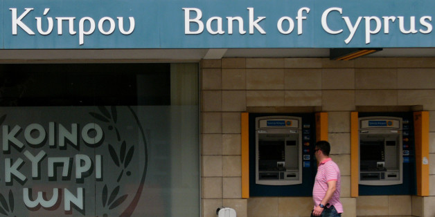 """A man passes outside of a branch of bank of Cyprus at a main shopping street in central capital Nicosia, Cyprus, Sunday, April 14, 2013. Cyprus' President Nicos Anastasiades has chided the central bank chief to not act in ways that """"catch the government by surprise,"""" but to move to stabilize the country's troubled banking sector. (AP Photo/Petros Karadjias)"""