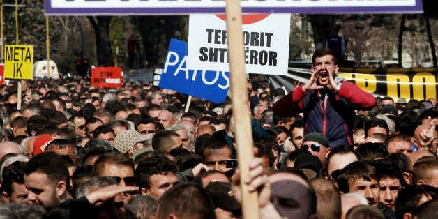 A protestor shouts slogans behind a placard reading Early Elections during a protest in front of the government building in Tirana on March 12, 2015, to demand the resignation of the Parliament speaker.  The Albanian opposition requests the resignation of Parliament Speaker Ilir Meta, the junior ally in the government coalition and that of Socialist Prime Minister Edi Rama following accusations from former Socialist MP Tom Doshi, that Meta had commissioned his assassination. Meta maintains that