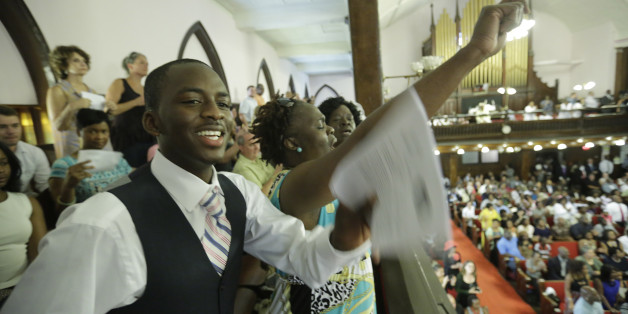 CHARLESTON, SC - JUNE 21:  Parishioners Shakur Francis, left, and Karen Watson-Fleming sing as they attend the first church service four days after a mass shooting that claimed the lives of nine people at the historic Emanuel African Methodist Church June 21, 2015 in Charleston, South Carolina. Chruch elders decided to hold the regularly scheduled Sunday school and worship service as they continue to grieve the shooting death of nine of its members including its pastor earlier this week.  (Photo