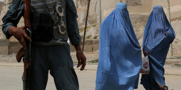 Two Afghan women walk past as a policeman stands guard in Ghazni on August 15, 2013. Taliban militants have kidnapped a female Afghan member of parliament, officials said on August 14, in the latest example of prominent women being targeted in the country. Fariba Ahmadi Kakar and her three children were taken at gunpoint on August 10 in the central province of Ghazni on the main highway from Kandahar city to Kabul. AFP PHOTO/ Rahmatullah ALIZADA        (Photo credit should read RAHMATULLAH ALIZADA/AFP/Getty Images)