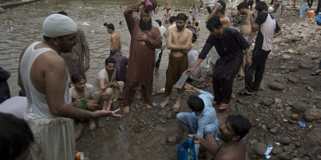 People cool themselves off at a stream in Islamabad, Pakistan as temperature increased during Ramadan, Monday, June 22, 2015. More than 100 people have died from heatstroke in the southern Pakistani port city of Karachi in the last two days, officials said Monday. (AP Photo/B.K. Bangash)