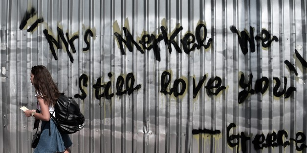 A young woman walks past a graffiti reading 'Mrs Merkel we still love you - Greece' in central Athens on June 19, 2015. The European Central Bank's decision-making governing council will hold an emergency session on June 19 to discuss a request from the Bank of Greece for an increase in liquidity to Greek banks. AFP PHOTO / ARIS MESSINIS        (Photo credit should read ARIS MESSINIS/AFP/Getty Images)
