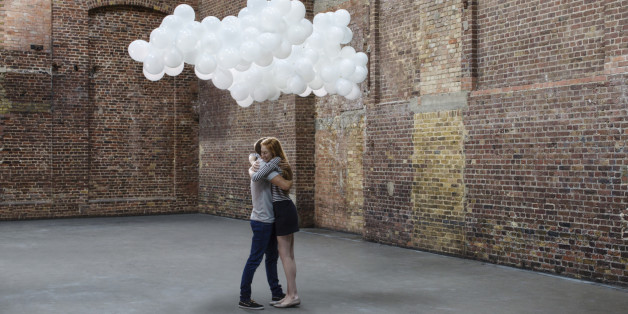 Couple hugging in empty warehouse with cloud made of balloons above heads