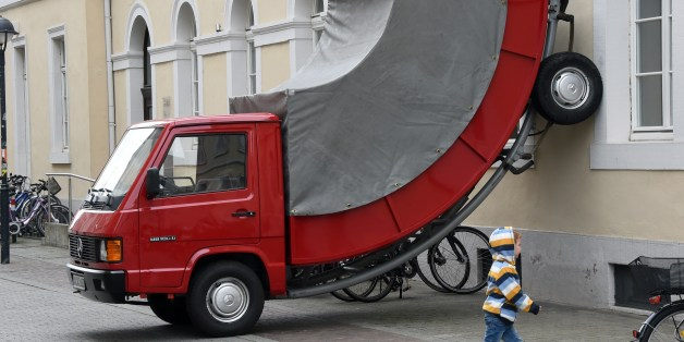 A child walks past the work 'Truck' by Austrian artist Erwin Wurm on June 21, 2015 in Karlsruhe, southwestern Germany. The work is part of the exhibition 'The City is the Star  Art at the Construction Site' running across the city until September 27, 2015.              AFP PHOTO / DPA / ULI DECK    +++    GERMANY OUY  RESTRICTED TO EDITORIAL USE, MANDATORY MENTION OF THE ARTIST UPON PUBLICATION, TO ILLUSTRATE THE EVENT AS SPECIFIED IN THE CAPTION        (Photo credit should read ULI DECK/AFP/Getty Images)