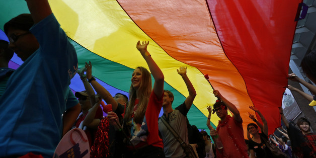 Participants march as they walk under a rainbow flag, a symbol of the gay rights movement, during a gay rally in Hong Kong Saturday, Nov. 9, 2013. Organizers say thousands of people are taking part in the annual Gay Pride Parade including representatives from more than 50 organizations as well as participants from the mainland and Taiwan, according to government radio. (AP Photo/Vincent Yu)