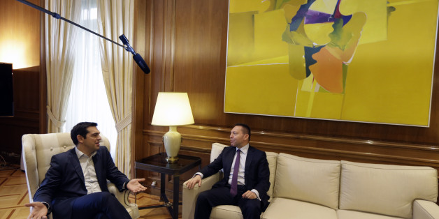 """Greece's Prime Minister Alexis Tsipras, left, speaks with Governor of the Bank of Greece Yannis Stournaras at Maximos Mansion in Athens, Friday, March 6, 2015. European Central Bank head Mario Draghi said the ECB """"stood ready"""" to once again permit Greek banks to use junk-rated Greek government bonds as collateral to get credit from the ECB. That would happen as soon as the bank assesses that Greece is likely to successfully complete a creditor review of its progress. (AP Photo/Thanassis Stavrakis)"""