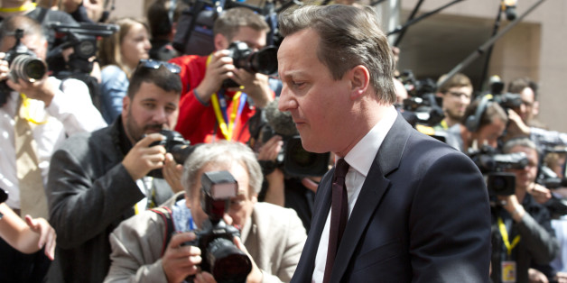 British Prime Minister David Cameron walks by the media as he arrives for an EU summit in Brussels