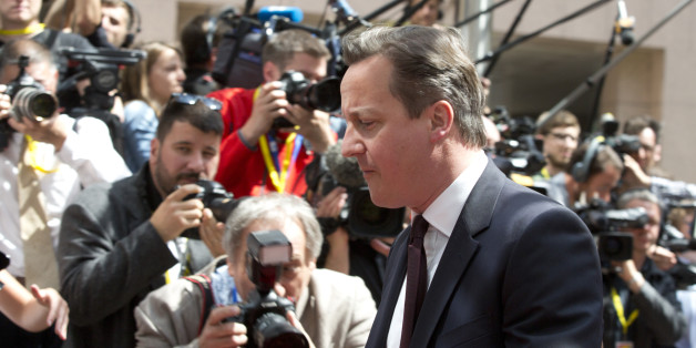 British Prime Minister David Cameron walks by the media as he arrives for an EU summit in Brussels on Thursday, June 25, 2015. Greece and its creditors launched a new round of talks in Brussels early Thursday in a fresh bid to unlock billions of euros in loans and save the country from bankruptcy. (AP Photo/Virginia Mayo)
