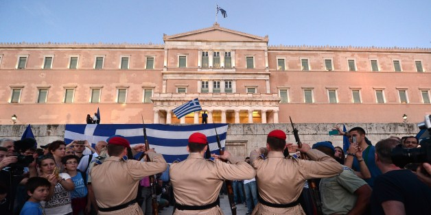 Presidental guards make their way through gathered crowds during a pro-European demonstration in front of the Greek parliament in Athens on June 22, 2015. Greece's international lenders raised hopes for a vital bailout agreement this week to save Athens from default and a possible euro exit, despite warning no deal was likely at an emergency summit.  AFP PHOTO / LOUISA GOULIAMAKI        (Photo credit should read LOUISA GOULIAMAKI/AFP/Getty Images)