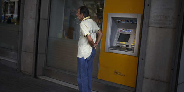 A man puts his wallet in his pocket after withdrawing euro notes from a bank machine in Athens, Thursday, June 25, 2015. The ECB approved a request from Athens to increase the amount of emergency liquidity Greek lenders can tap from the country's central bank. Worried Greeks have been withdrawing their money from their country's banks, fearing the imposition of restrictions on banking transactions. An estimated more than 4 billion euros ($4.5 billion) left Greek banks last week. (AP Photo/Daniel Ochoa de Olza)