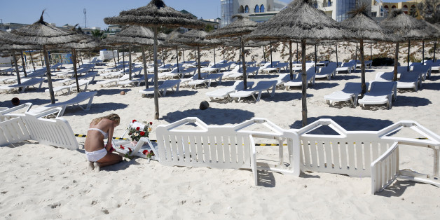 A ypong woman  lays a flowers at the scene of a shooting  in Sousse, Tunisia, Saturday, June 27, 2015. The morning after a lone gunman killed at tens of people  at a beach resort in Tunisia, busloads of tourists are heading to the nearby Enfidha-Hammamet airport hoping to return to their home countries. (AP Photo/Darko Vojinovic)