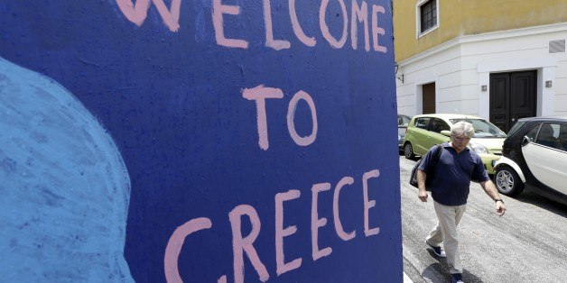 A man passes graffiti in the Plaka tourist district in Athens, Friday, June 5, 2014. Greek Prime Minister Alexis Tsipras is set to address an emergency session of Parliament over the country's struggles to get a deal with creditors, a day after his government opted to delay loan repayments to the International Monetary Fund — a gambit that has rattled markets all around the world (AP Photo/Thanassis Stavrakis)
