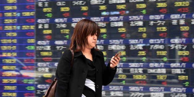 A woman uses her smart phone before a share prices board in Tokyo on April 9, 2015. Japan's share prices rose 147.91 points to close at 19,937.72 points at the Tokyo Stock Exchange, thanks to a weaker yen, with the benchmark Nikkei index approaching the psychologically important 20,000 level last seen in 2000.   AFP PHOTO / Yoshikazu TSUNO        (Photo credit should read YOSHIKAZU TSUNO/AFP/Getty Images)