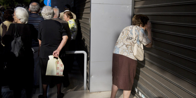 An elderly woman looks through the closed shutters of a bank as others, who usually get their pensions at the end of the month, wait outside a closed bank in Athens, Monday, June 29, 2015. Greece's five-year financial crisis took its most dramatic turn yet, with the cabinet deciding that Greek banks would remain shut for six business days and restrictions would be imposed on cash withdrawals. (AP Photo/Petros Giannakouris)