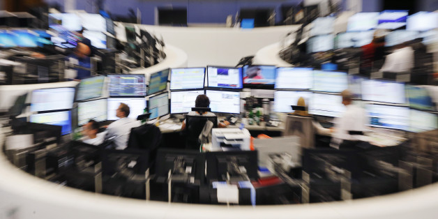 Traders sit in front of their screens at the stock market in Frankfurt, Germany, Monday, June 29, 2015. The German stock index DAX lost around 500 point right after the opening of the stock market. (AP Photo/Michael Probst)