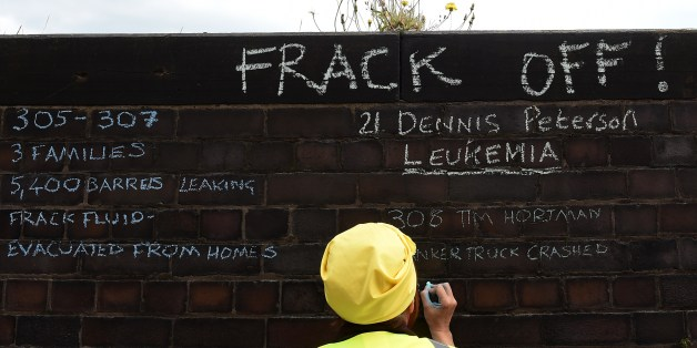 An anti-fracking demonstrator writes messages on a wall outside Lancashire County Hall in Preston, northwest England, on June 23, 2015 during a demonstration to protest against the applications from energy firm Cuadrilla to start two fracking operations on nearby sites. Lancashire County Council were expected to vote on June 24 on of one of two applications from energy firm Cuadrilla to start fracking operations at the nearby Little Plumpton and Roseacre Wood sites. Fracking or hydraulic fracturing is a process used to extract shale gas by blasting a high-pressure mixture of water, sand and chemicals deep underground to release hydrocarbons trapped between layers of rock.  AFP PHOTO / PAUL ELLIS        (Photo credit should read PAUL ELLIS/AFP/Getty Images)